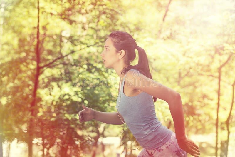 跑在夏天森林里的妇女 免版税库存照片