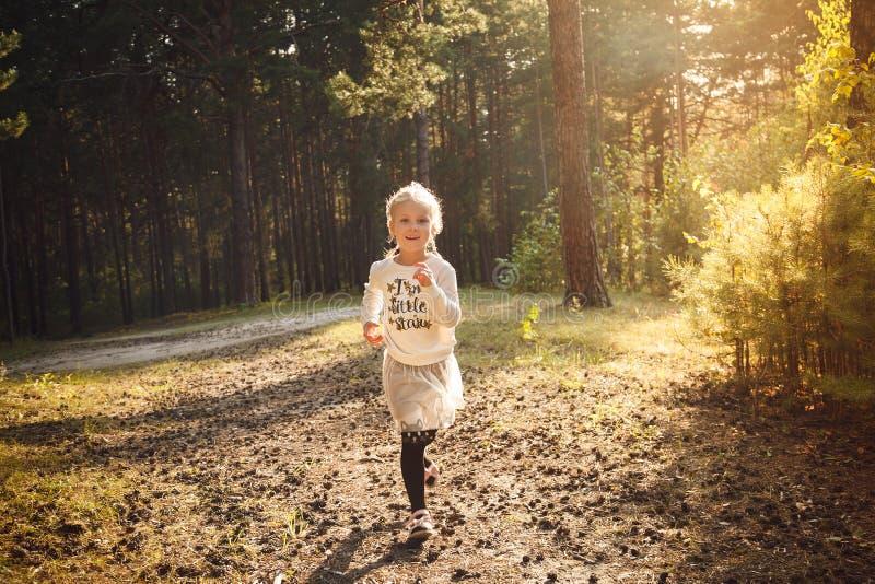 跑在夏天森林里的愉快的小女孩 库存图片