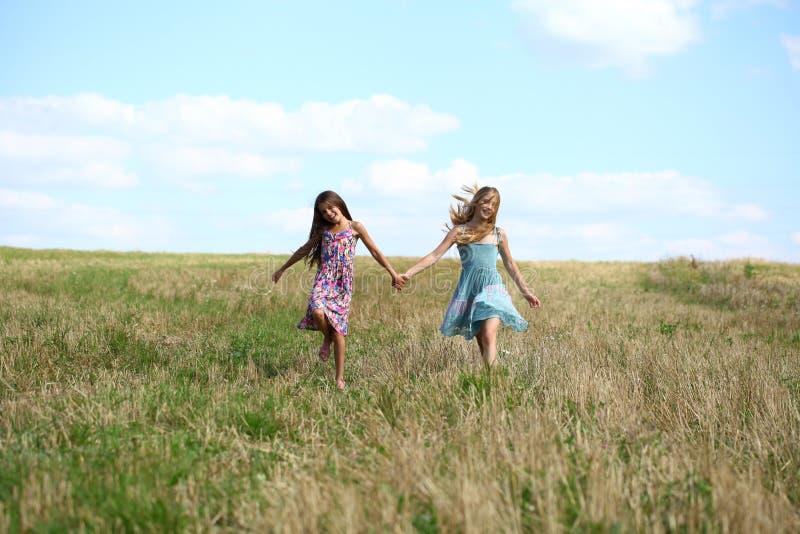 跑在夏天领域的两个小女孩 库存图片