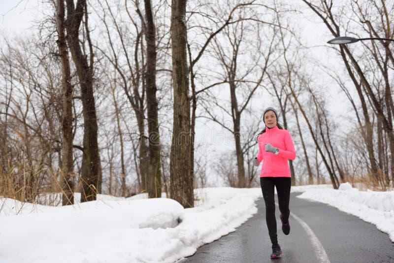 跑在多雪的城市公园-冬天健身的妇女 免版税库存图片