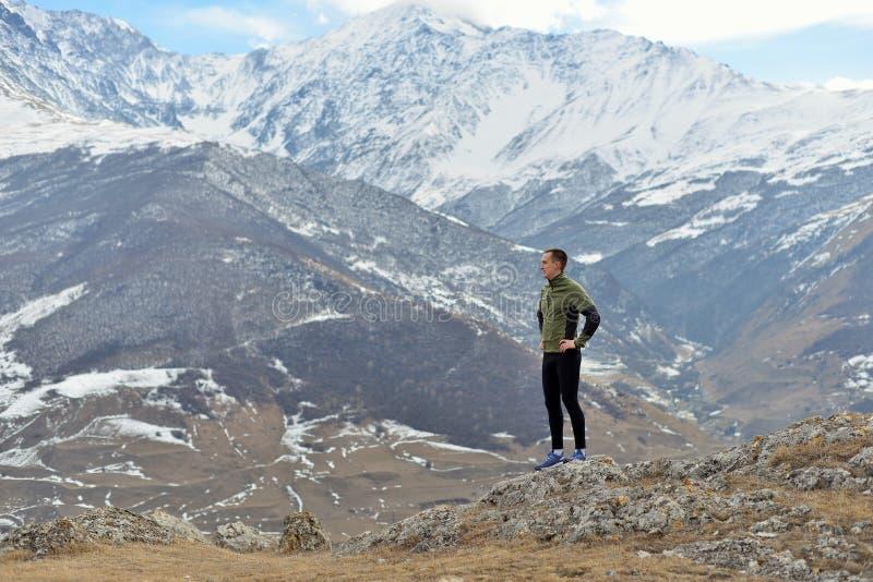 跑在多雪的山附近的运动的年轻人 免版税库存图片