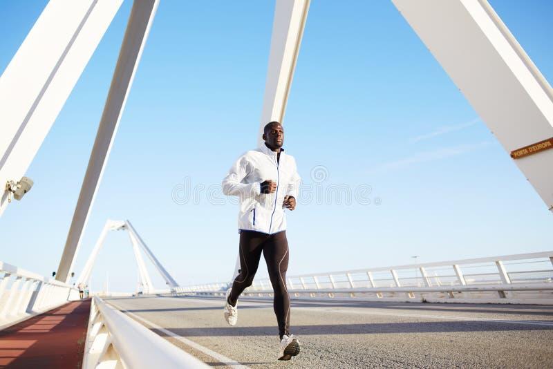 跑在大桥梁的一位美丽的深色皮肤的运动员 免版税库存照片