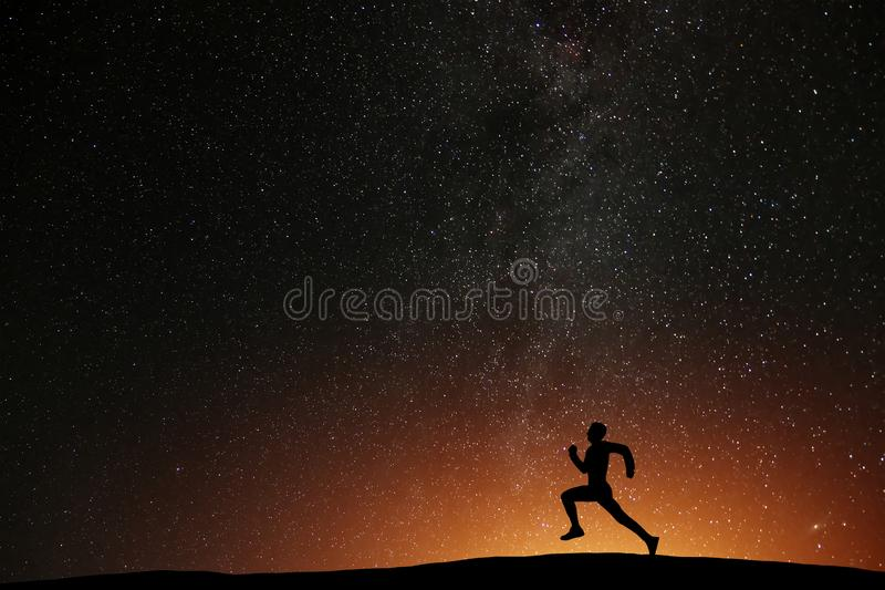 跑在小山的赛跑者运动员与美好的繁星之夜 免版税库存图片