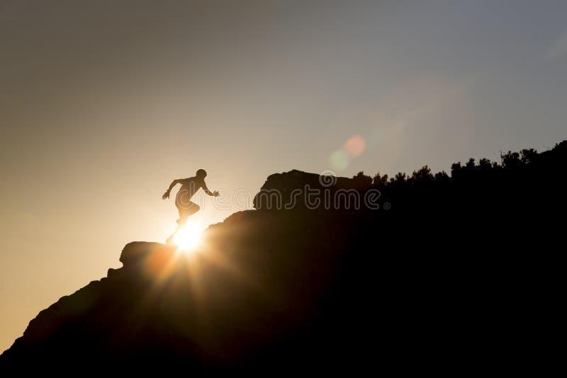 跑在山的足迹连续运动员,在日落 免版税库存图片