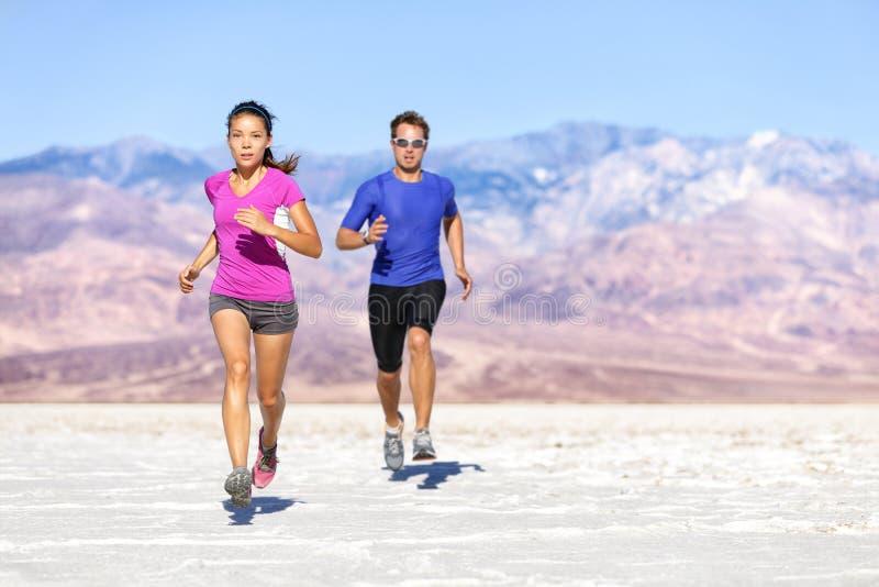 跑在干燥沙漠风景的赛跑者足迹 免版税库存图片