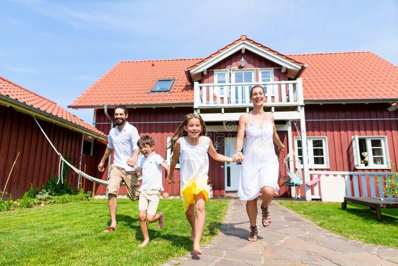 跑在房子前面的草甸的愉快的家庭 免版税库存图片