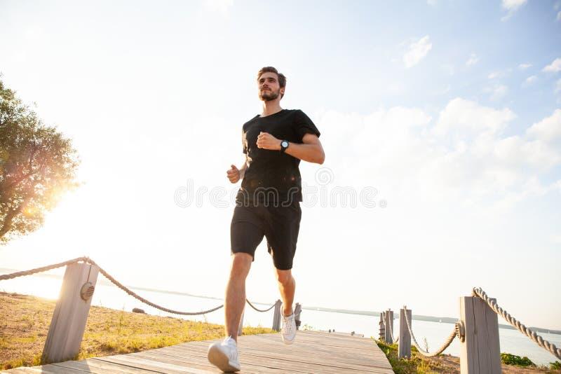 跑在散步的健康年轻人全长射击  冲刺公的赛跑者户外 免版税库存图片
