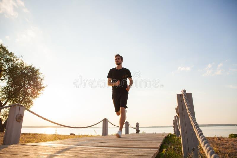 跑在散步的健康年轻人全长射击  冲刺公的赛跑者户外 图库摄影