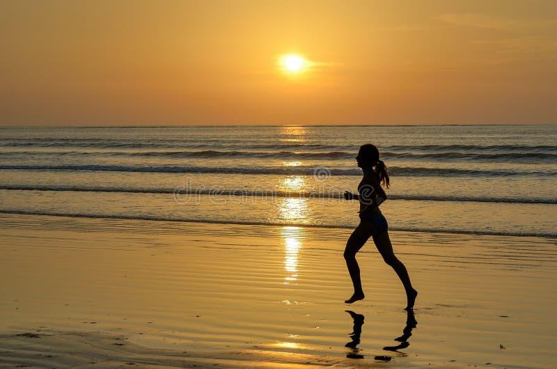 跑在日落海滩的妇女慢跑者剪影 免版税库存图片