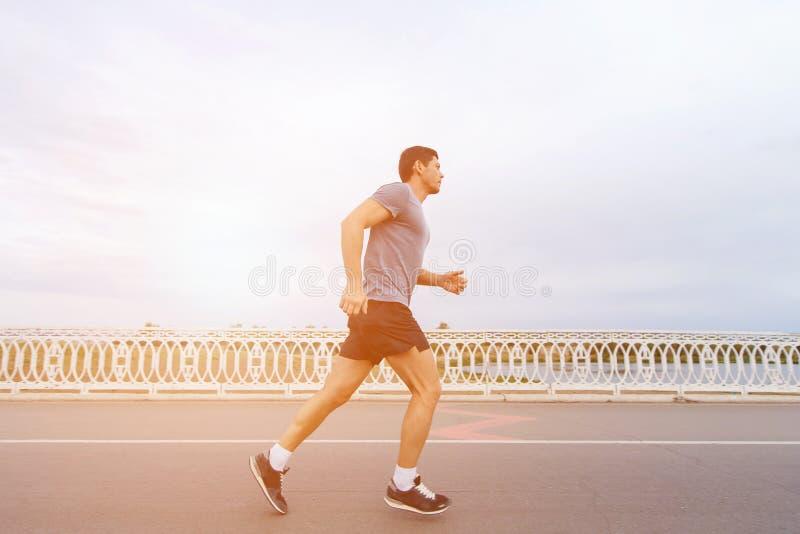 跑在日落的一个英俊的年轻人在河沿的篱芭旁边 图库摄影