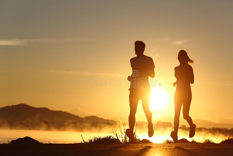 跑在日落的夫妇的剪影 免版税库存照片
