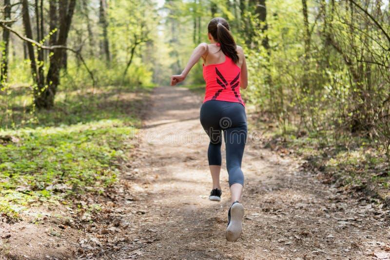 跑在春天晴朗的森林里的活跃妇女 免版税图库摄影