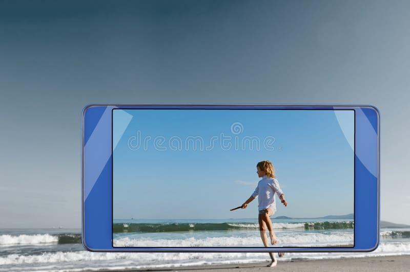 跑在智能手机的框架的海滩的男孩 免版税图库摄影