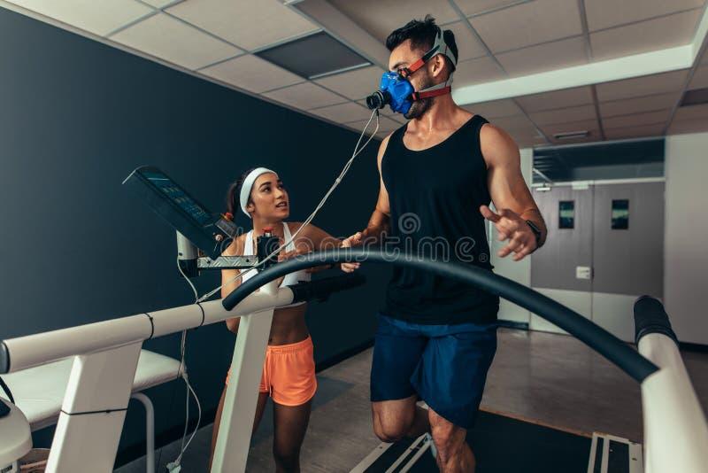 跑在有女性教练员的踏车的运动员 库存图片