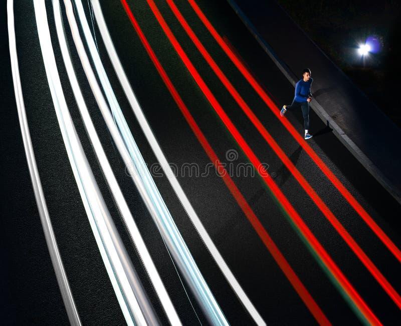 跑在有汽车轻的足迹的夜路的年轻体育人 健康生活方式和都市体育概念 免版税图库摄影