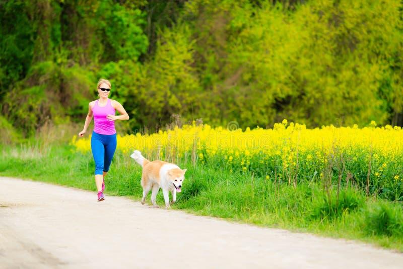 跑在有狗的夏天公园的妇女 免版税库存照片