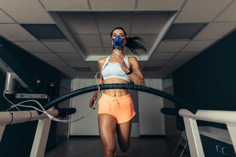 跑在有面具的踏车的适合的妇女 库存图片