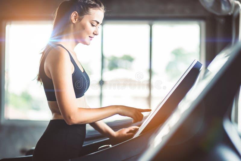跑在机器踏车的健康人民在健身健身房,工作 免版税库存照片