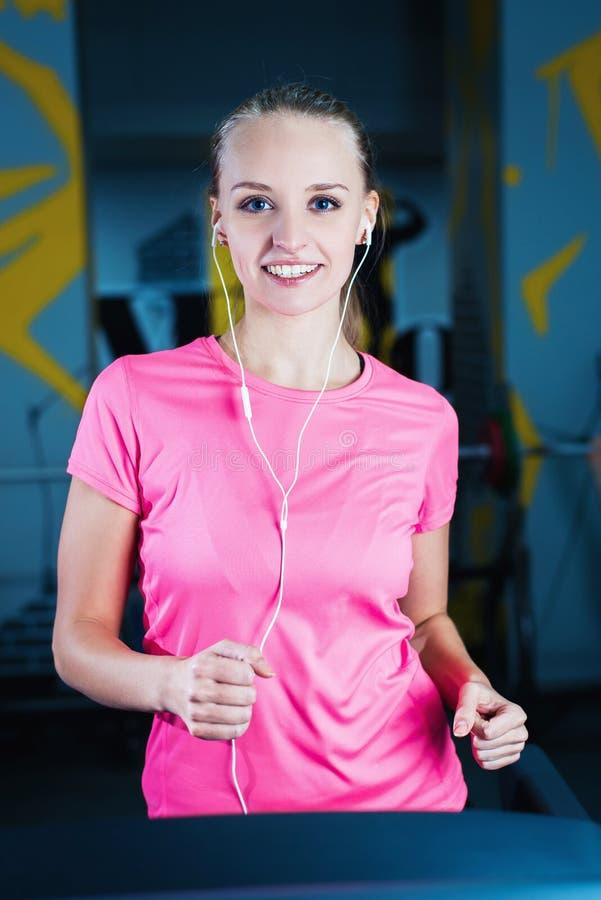 跑在机器踏车的可爱的健身女孩 做锻炼的俏丽的女孩在现代健身健身房 免版税库存图片