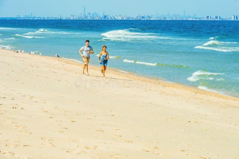 跑在桑迪勾子的年轻夫妇靠岸,新泽西,美国 库存照片