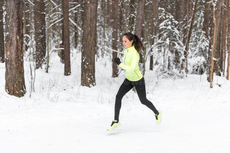 跑在森林的年轻人适合的运动员妇女冲刺在冬天训练期间外面在冷的雪天气 免版税图库摄影