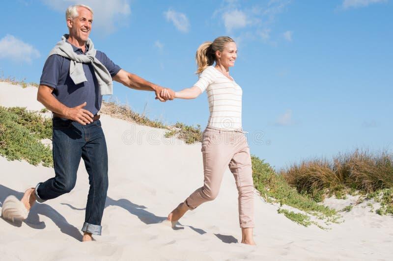 跑在沙丘下的夫妇 免版税库存图片