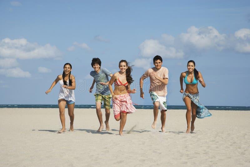 跑在沙滩的愉快的少年 免版税库存图片