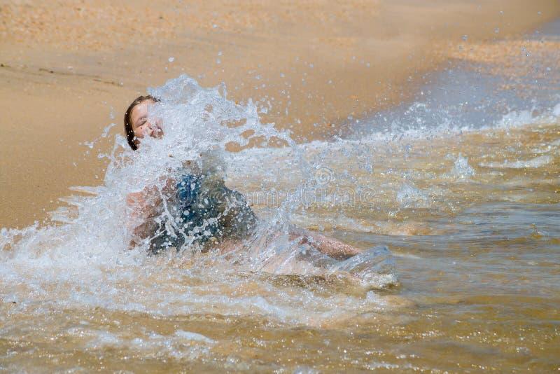 跑在波浪的愉快的孩子在海滩的暑假时在海洋学会海岸的女孩游泳 库存照片