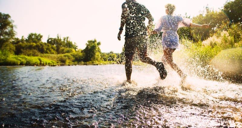 跑在浅水区的愉快的夫妇 库存图片