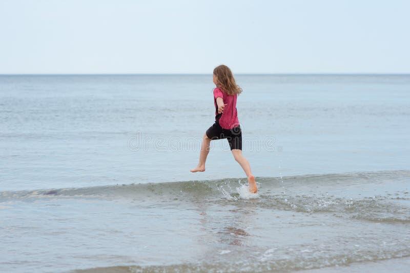 跑在海和使用与波浪的愉快的女孩 图库摄影