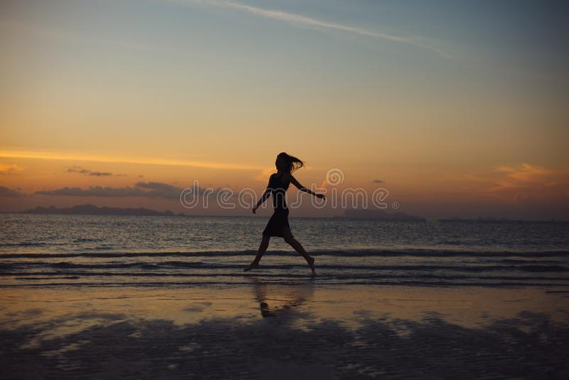 跑在海洋海滩的妇女剪影 免版税库存照片