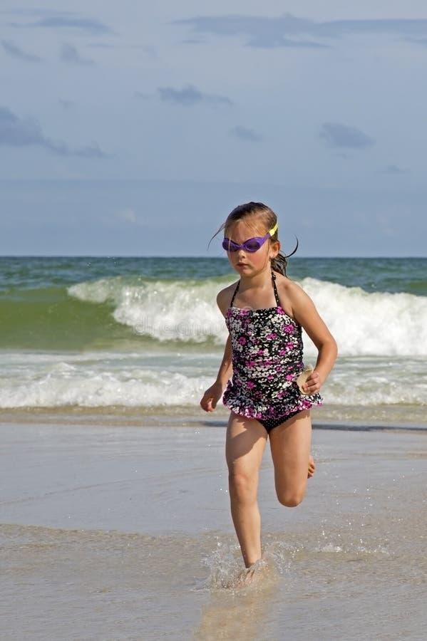 跑在海浪的孩子。 库存图片