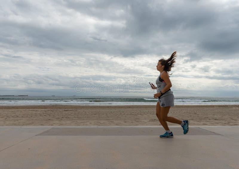 跑在海滩前面的Atlethic妇女 免版税图库摄影