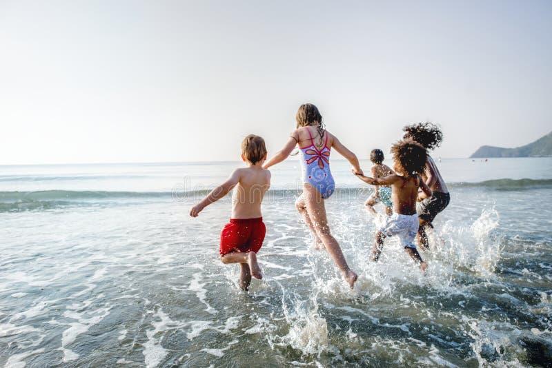 跑在海滩的不同的孩子 免版税库存图片