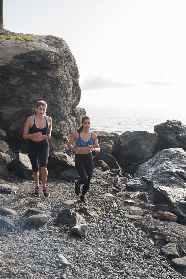 跑在海滩的两名妇女在岩石附近 库存照片