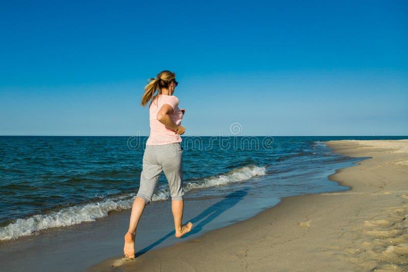 跑在海滩的中年妇女 免版税库存图片