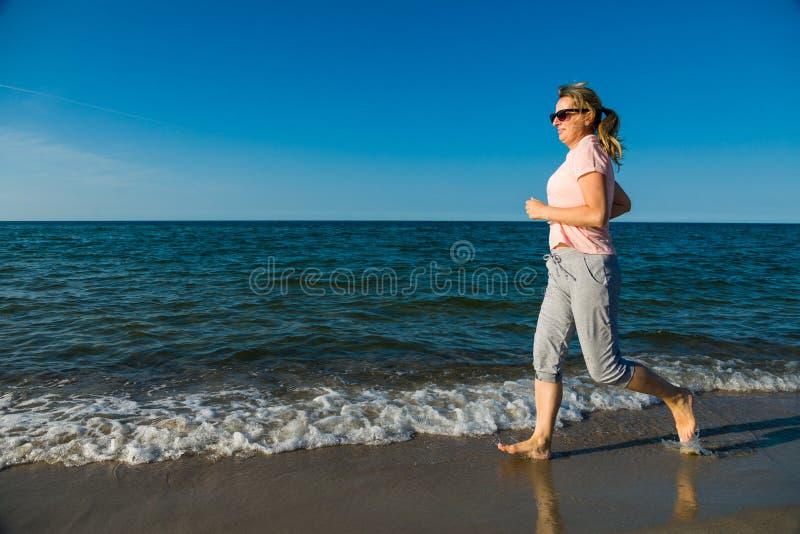 跑在海滩的中年妇女 库存照片