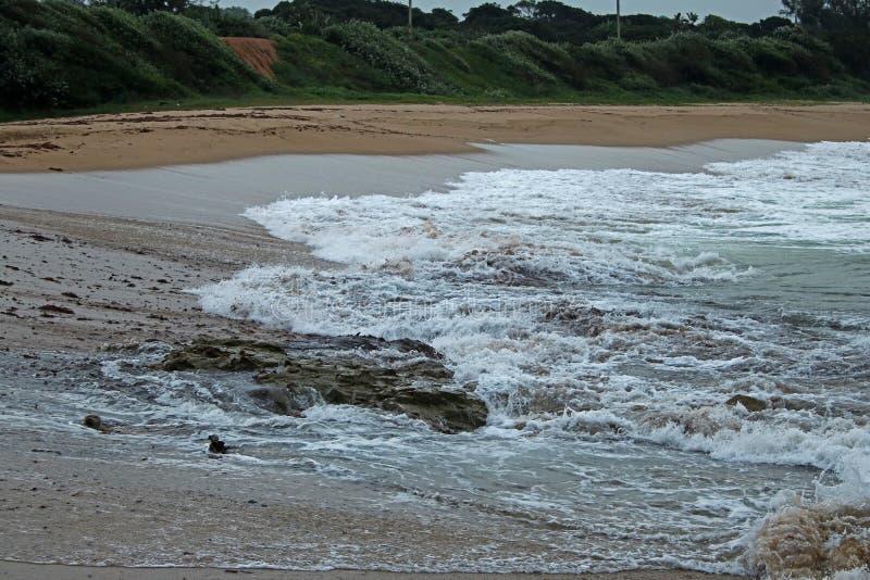 跑在海滩的岩石的回流 免版税库存图片