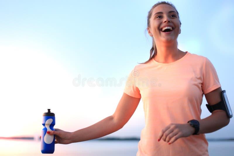 跑在海滩的年轻可爱的运动的健身妇女户外在日落或日出 免版税库存图片