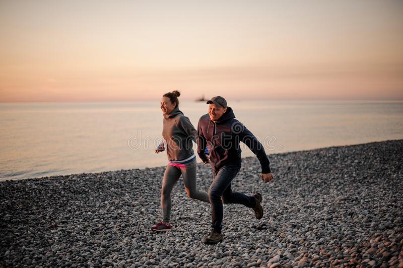 跑在海滩的愉快的夫妇握手 免版税库存照片