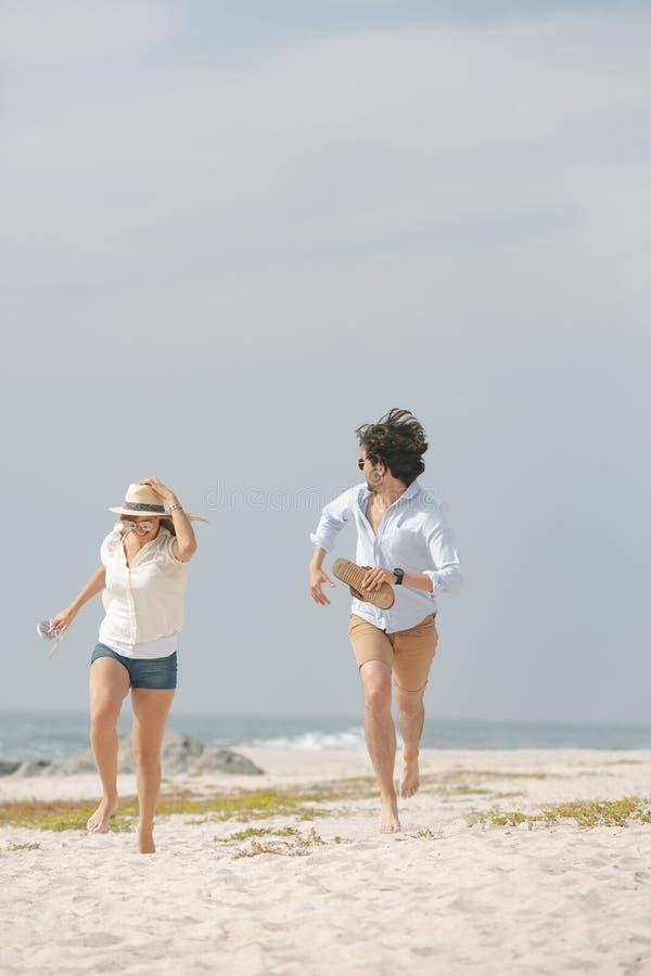 跑在海滩的愉快的白种人夫妇在好日子 免版税库存图片