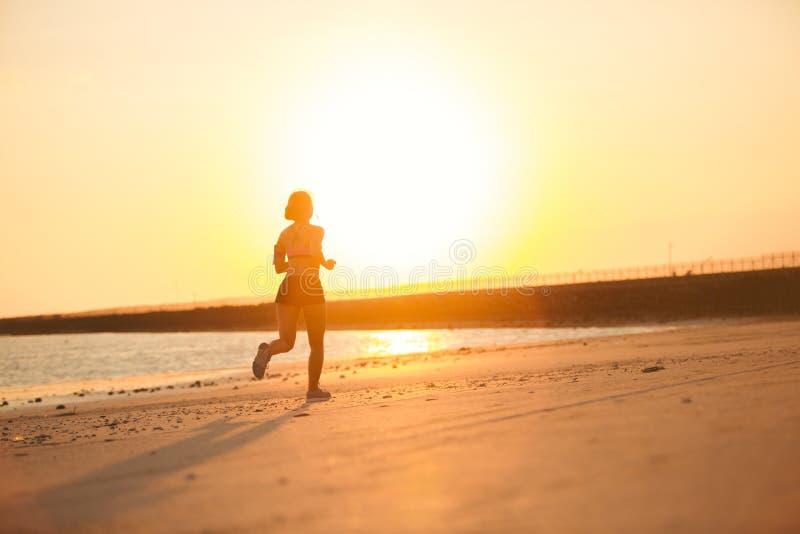 跑在海滩的母慢跑者剪影反对 库存照片