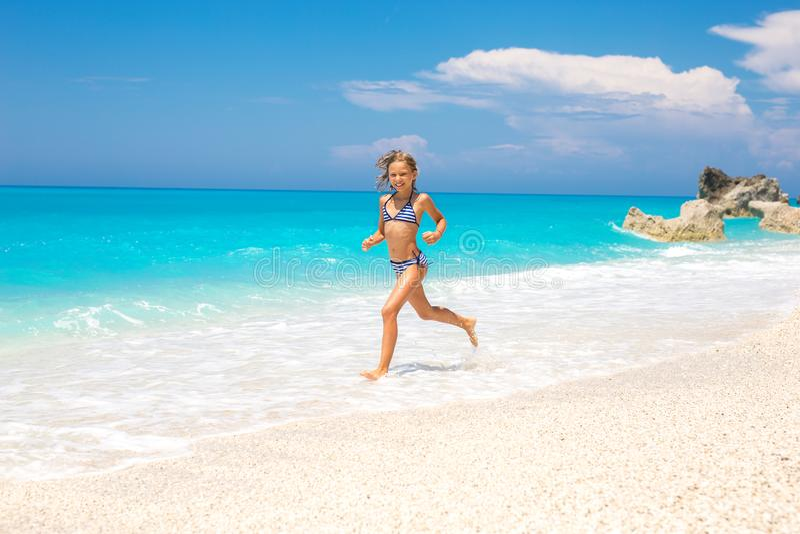 跑在海滩的美丽的小女孩 免版税图库摄影