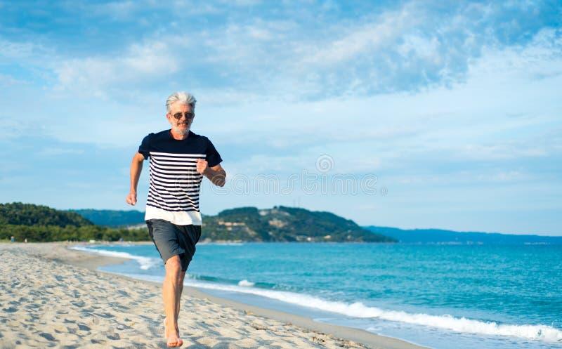 跑在海滩的老人 免版税库存图片