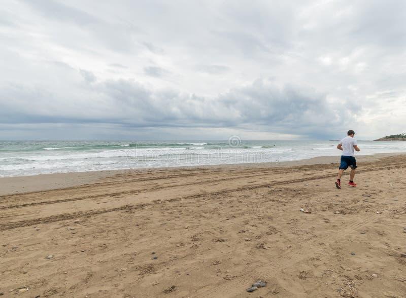 跑在海滩的Atlethic人 库存照片