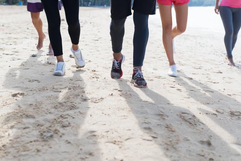 跑在海滩脚特写镜头体育赛跑者的小组青年人跑步制定出一起训练的队 库存图片