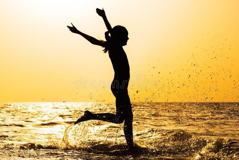 跑在海的女孩的剪影在日落 库存图片
