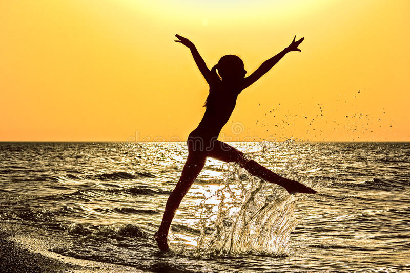 跑在海的女孩的剪影在橙色日落 库存照片