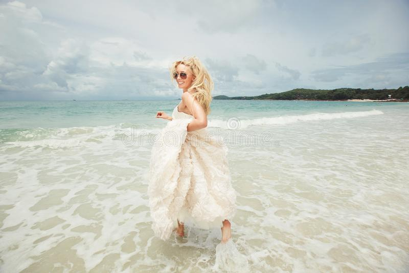 跑在海的婚礼礼服的少妇转回去 海滩的幸运和滑稽的新娘 库存照片