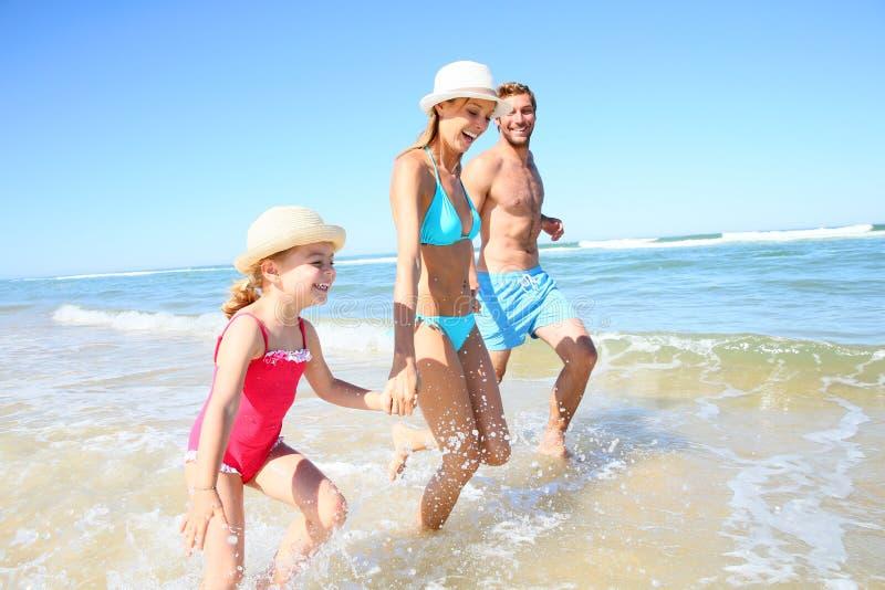 跑在海的年轻愉快的家庭 图库摄影